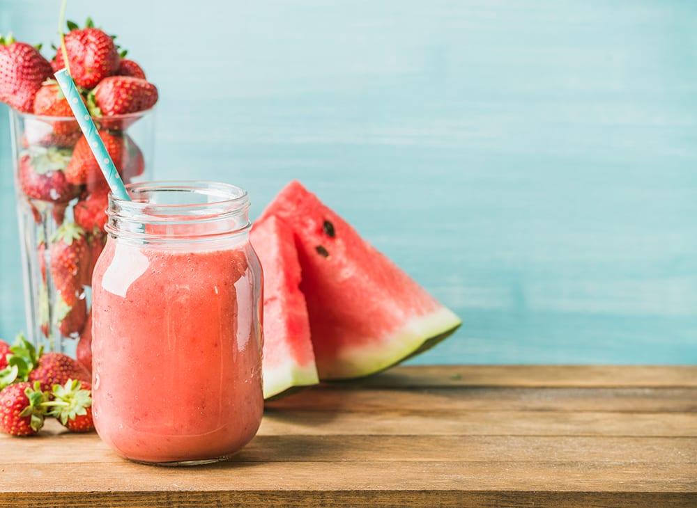 Smoothie aux fruits rouges fraîchement mélangés dans un bocal en verre avec de la paille. Fond bleu turquoise, espace de copie